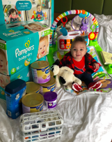 Smiling baby surrounded by diapers and formula